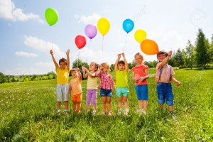 29409381-seven-children-with-balloons-in-green-field-during-summer-time-Stock-Photo