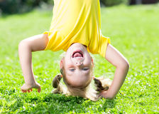 child-girl-standing-upside-down-her-head-happy-grass-summer-59361495